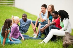 Group of teenage students sitting in a park on grass.